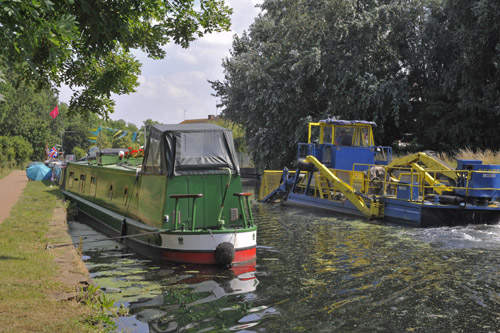 An elevator on the front of the weed cleaning blue boat attempts to remove Duckweed.