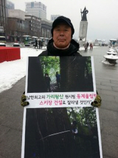Kijun Kim demonstrating against destruction of forest for Olympics
